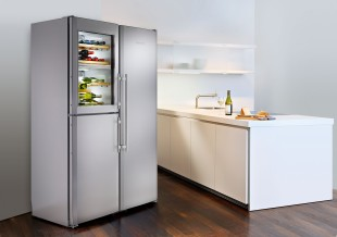 The stainless steel appliance stands in contrast to the white kitchen island and the wooden floor.